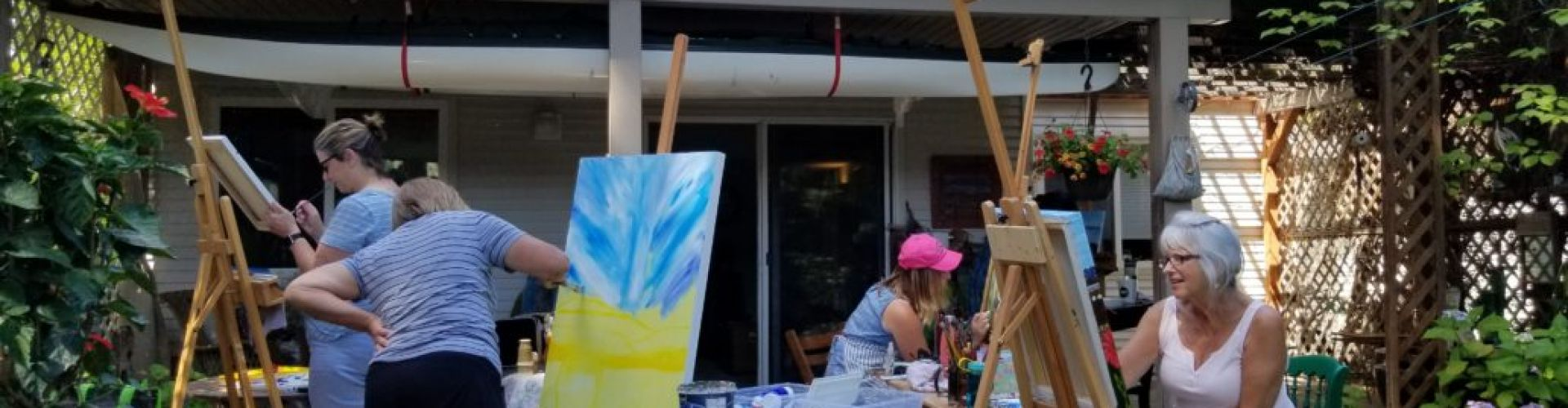A group of people painting on canvasses outside of a house, they are at one of the classes of Linda Lovisa.