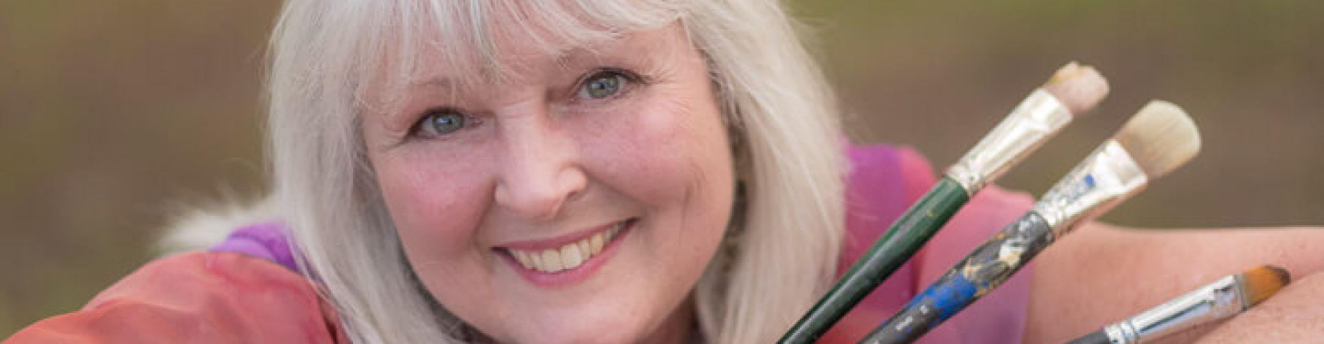 A close-up shot of Linda Lovisa while holding three paint brushes.