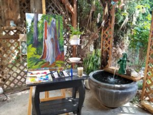 a canva painted on a tabe, it has brushes, colour and the tools to paint. Beside the table, there is a small fountain.