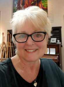 close-up portrait of Linda Lovisa, wearing black-rimmed reading glasses, a silver locket and a black shirt, and she has short white hair, with her art studio in the background.