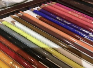 A close up look at colourful art pencil crayons lying flat on a surface, some of the tools Linda Lovisa uses to teach children in her art classes