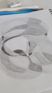 A doodle done with a pencil, with varying shades of grey, and done with more curving and circular lines, a piece from a Linda Lovisa class