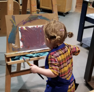 A young child wearing an apron paints scribbles across a canvas on an easel with purple paint while in Canadian artist Linda Lovisa art studio